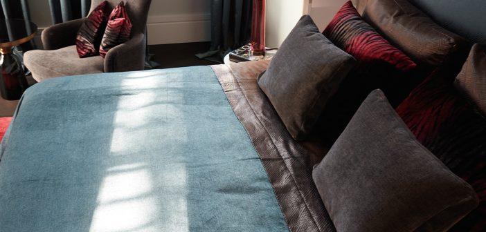 Bett mit blauer Tagesdecke
