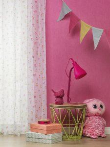 pinkfarbene Tapete und weiße Vorhänge mit Blümchenmuster