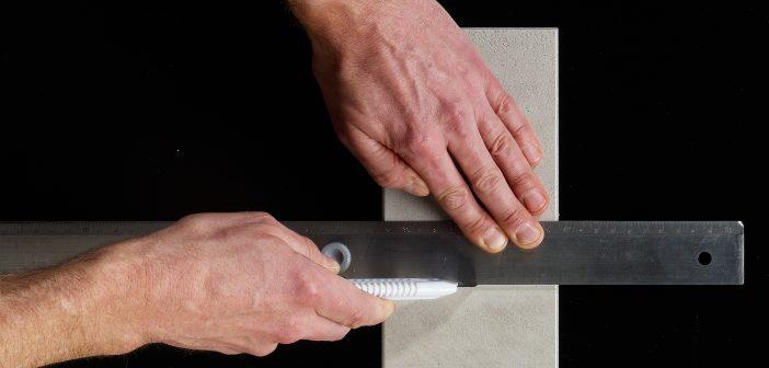 """Einfach mit dem Cuttermesser entlang einer Führungsschiene durch oder in die """"Betonschicht"""" schneiden."""